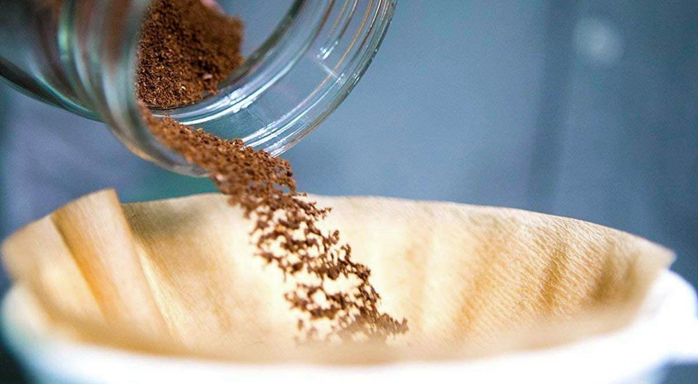 ground coffee poured from a mason jar into a coffee filter