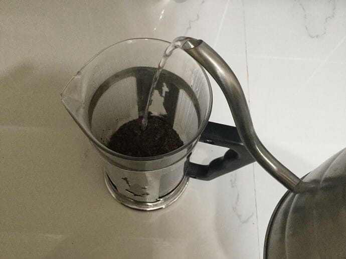 Pouring hot water into the French Press over coffee grounds