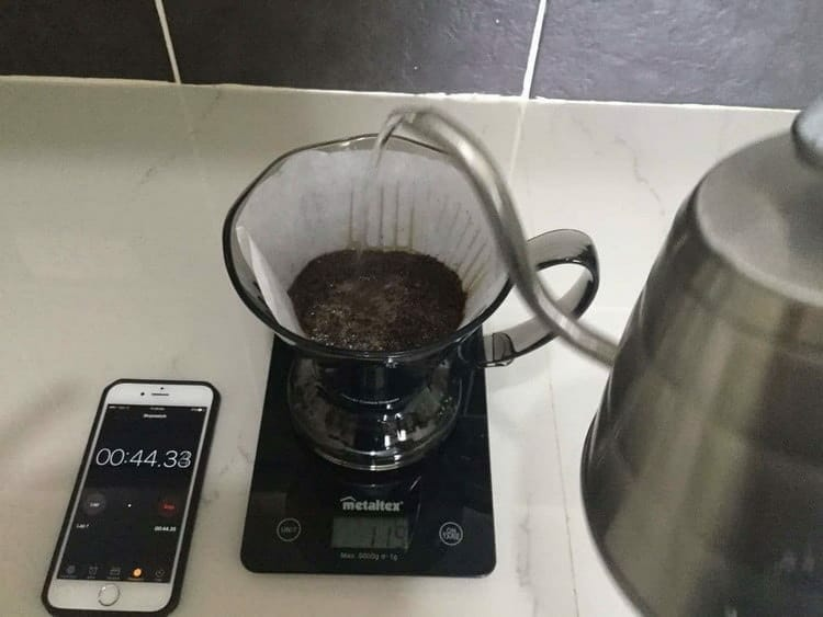 Slowly pouring water over coffee grounds