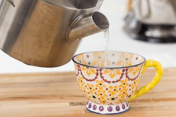 pouring boiling water from a kettle into a coffee cup