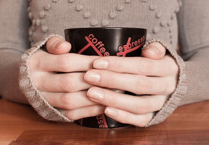 women holding a coffee cup with both hands