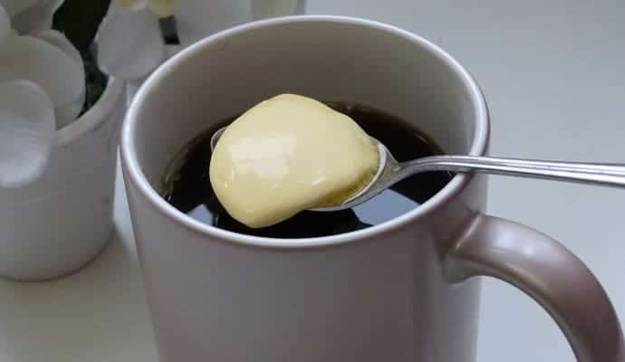 adding butter to coffee