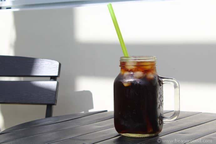 Coffee in a Mason Jar with a green straw