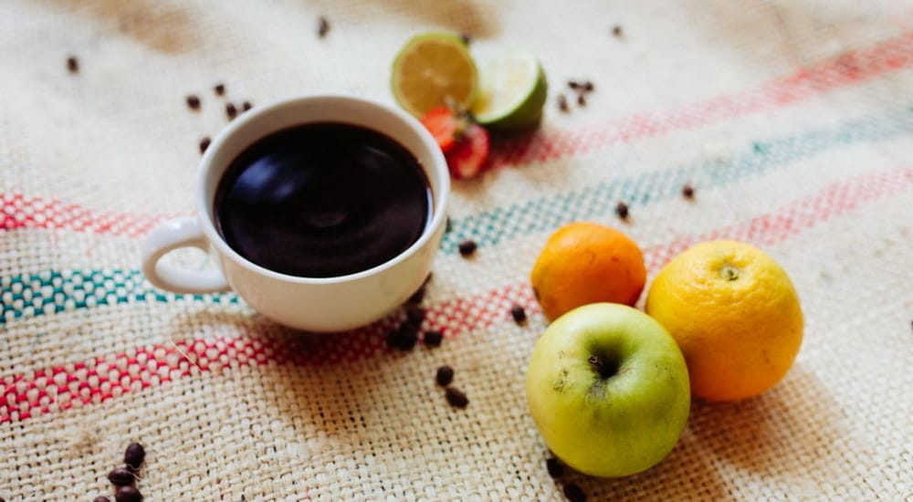 Cup of black coffee with acidic fruits on a table