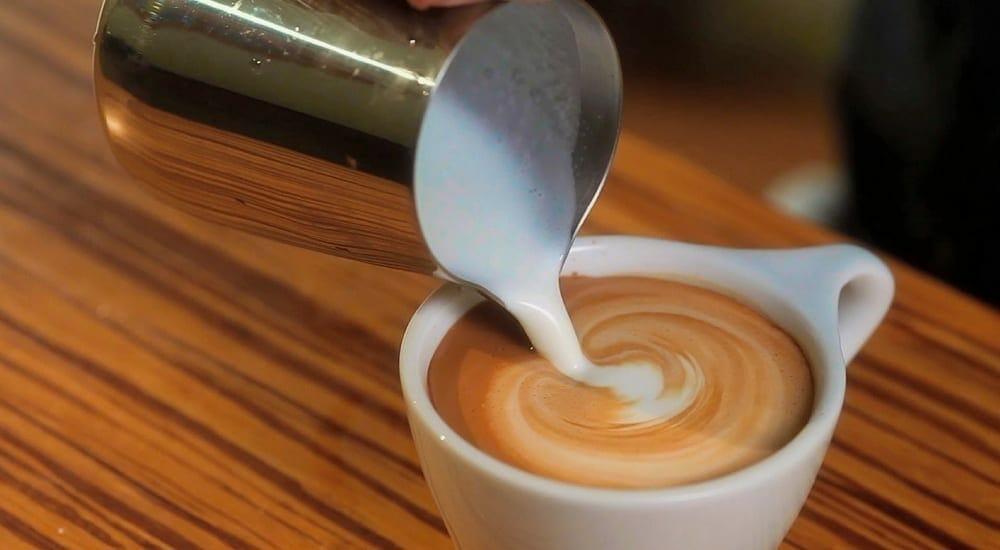 pouring milk onto a cappuccino
